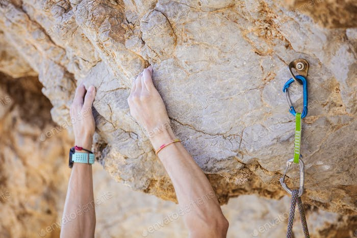 Closeup of climber's hands on cliff