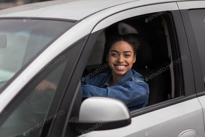 Schöne junge glückliche lächelnde Frau, die neues Auto oder Auto-Blogger fährt, schießt neues Video