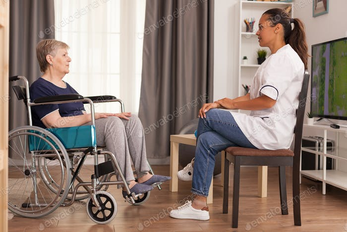 Caregiver talking with a disabled woman