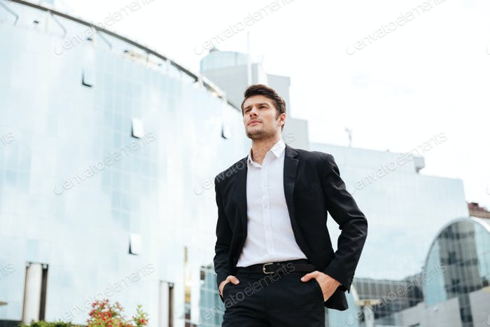 Confident young businessman walking in the city