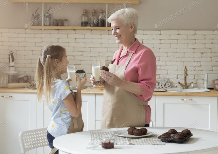 Adorable girl with her grandmother eating freshly baked muffins and drinking milk in kitchen