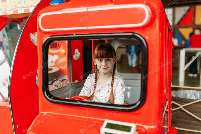 Little girl plays a bus driver, game machine