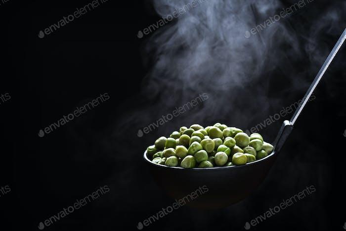 Gekochte Erbsen in einer Küchenkelle mit steigendem Dampf