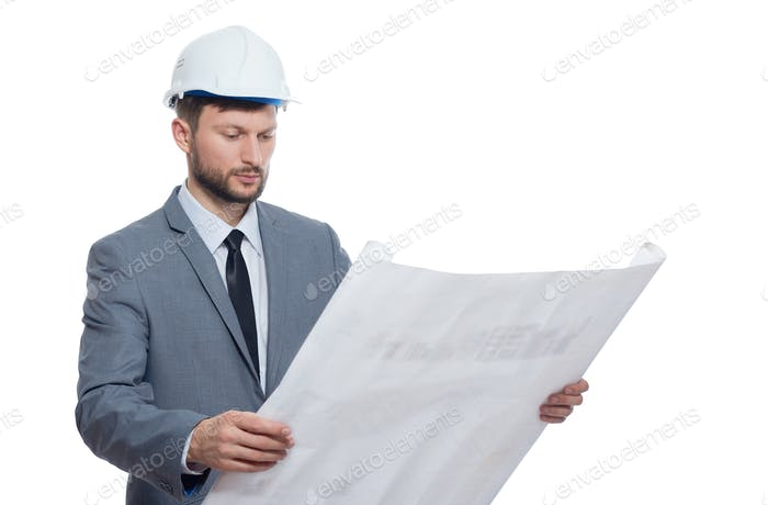 Engineer in safety hat reading architecture plan