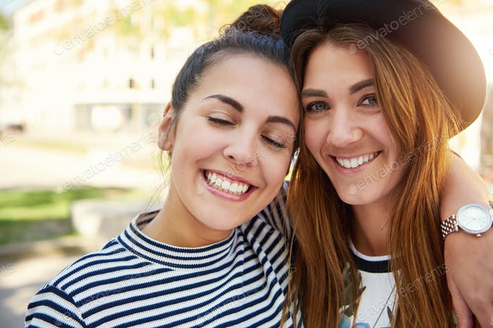 Two cute smiling young girl friends
