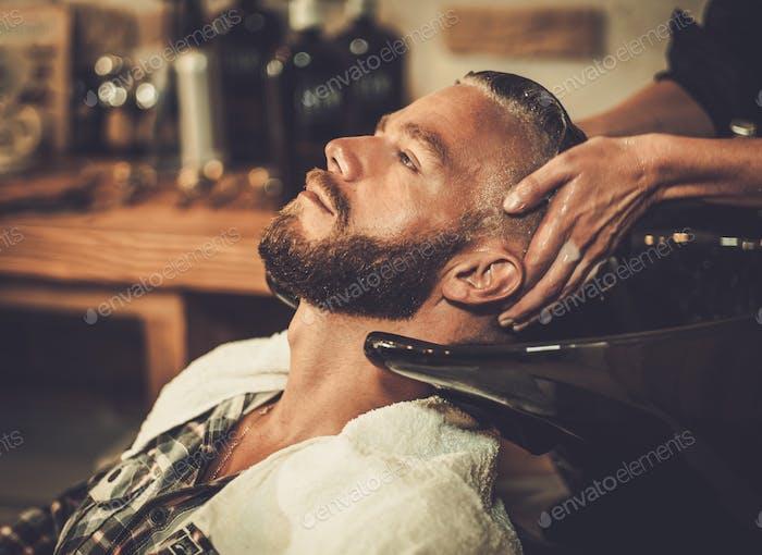 Парикмахер мытья волос клиента в парикмахерской