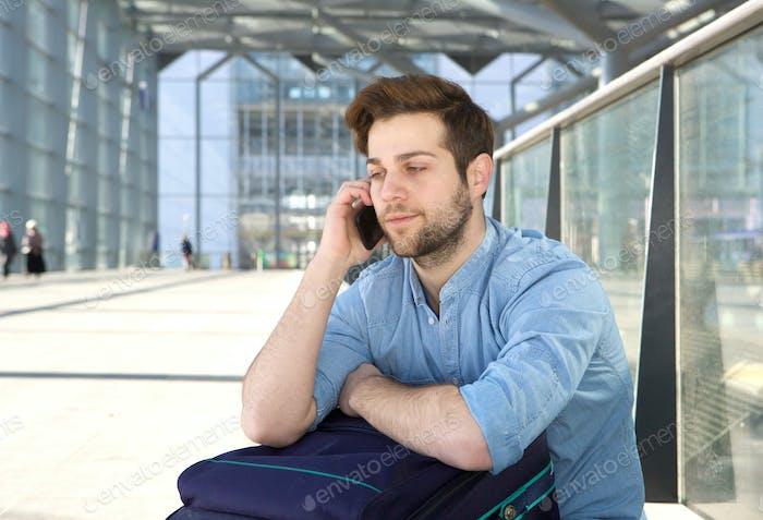 Man sitting on floor talking on mobile phone