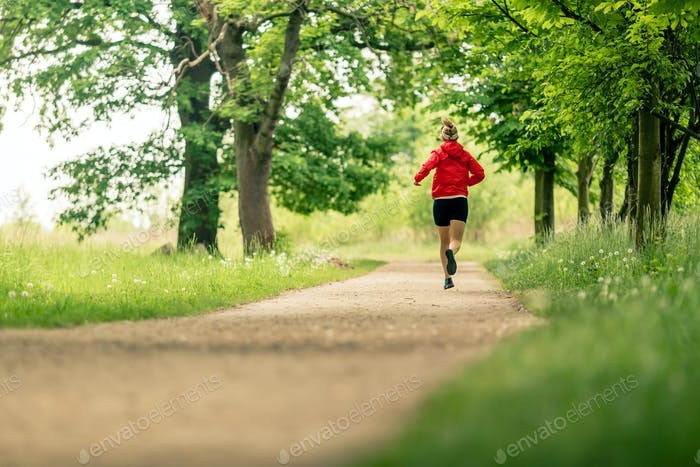 Running woman, enjoying summer day in park