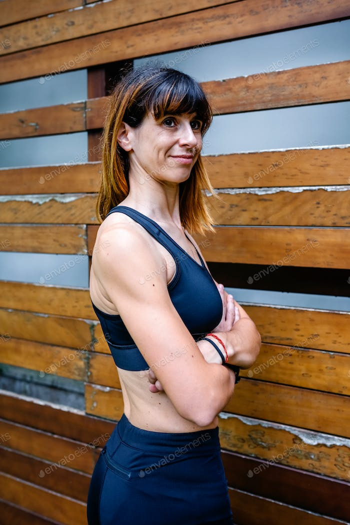 Cheerful female athlete in front of a wooden background