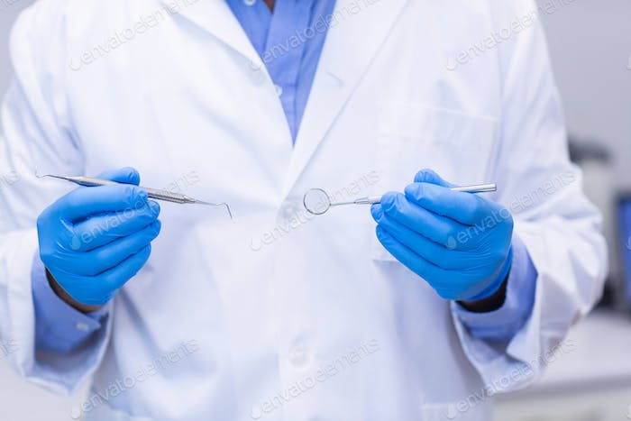 Dentist holding dental tools at dental clinic