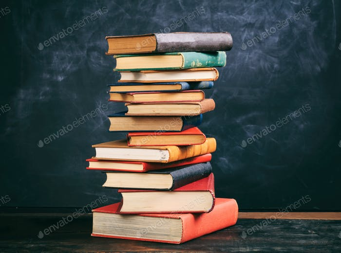 Vintage books stack on blackboard background