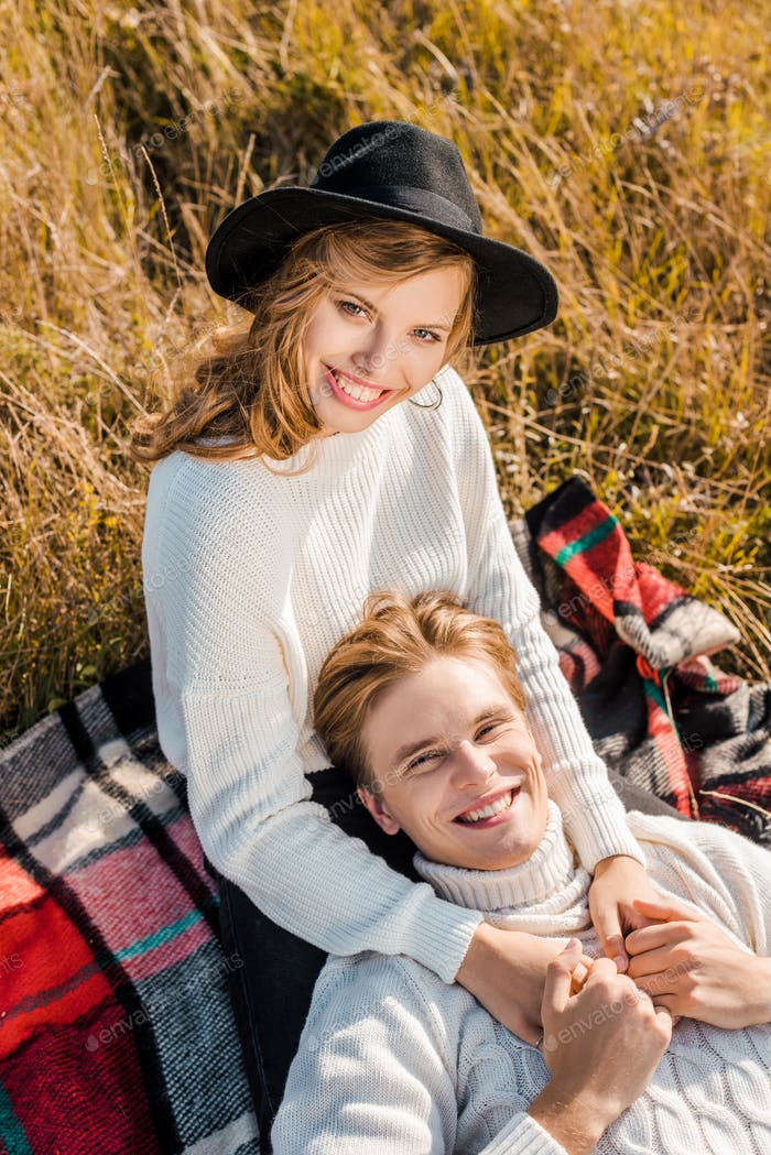 Happy Young Couple Looking at Camera on Rural Meadow