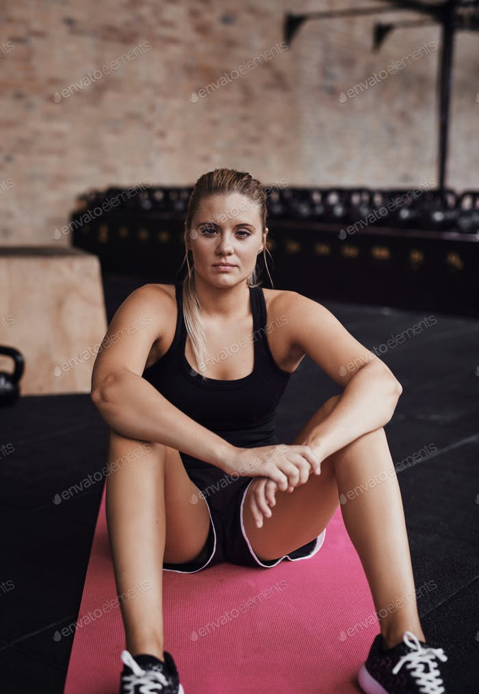 Confident young woman sitting on the floor of a gym