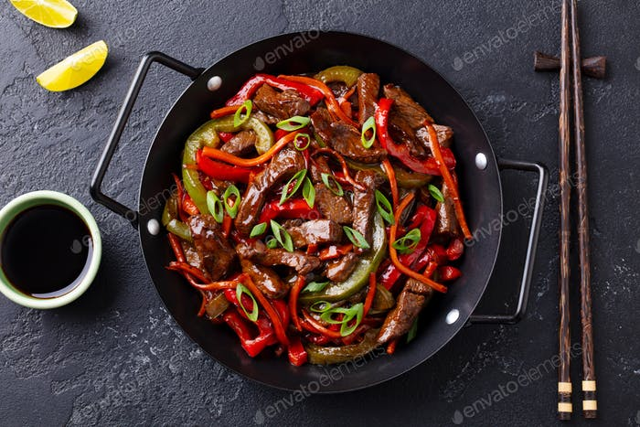 Beef and Vegetables Stir Fry in a Pan. Dark Background. Close up. Top view.