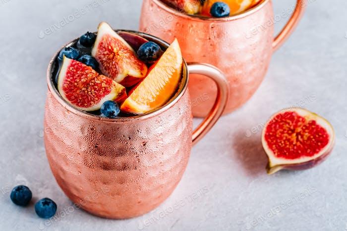 Fig Moscow Maultier eiskalter Cocktail in Kupferbecher mit Blaubeeren und Orange