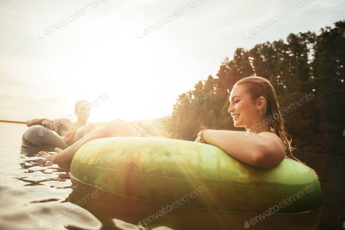 Young woman floating in an innertube at sunset