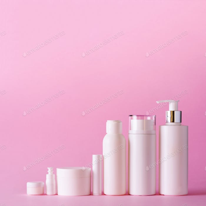 White cosmetic tubes on pink background with copy space. Skin care, body treatment, beauty concept