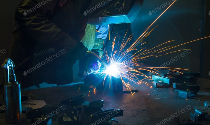 Close-up image of industrial worker at the factory welding.