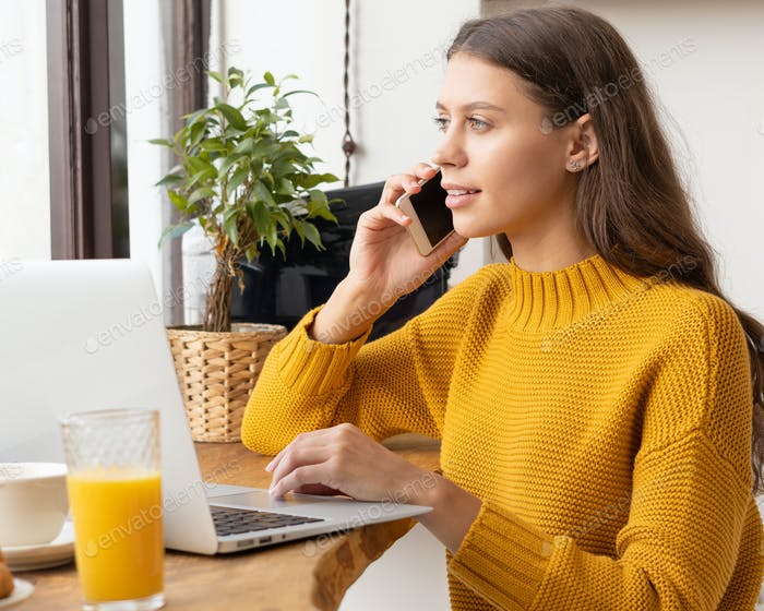 Digital nomad. Young female entrepreneur talking on mobile phone