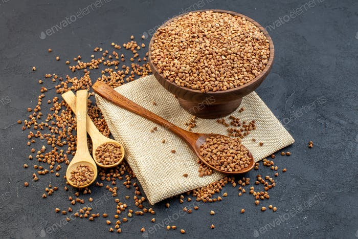 front view brown buckwheat inside plate with pair of spoons on dark background cereals groats food