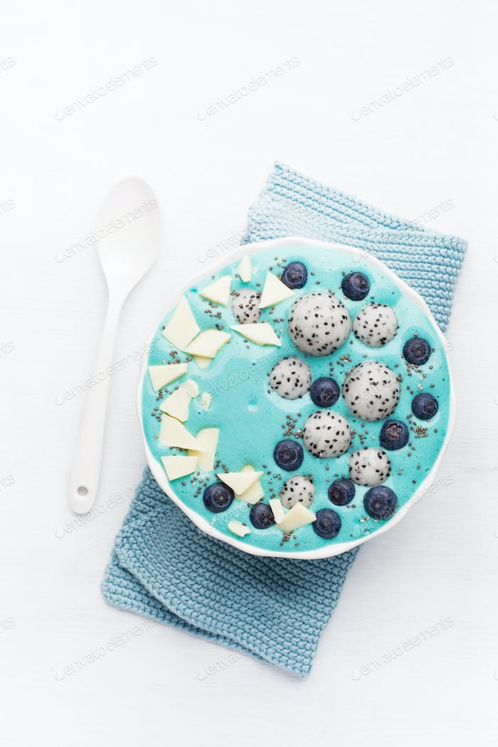 healthy blue spirulina smoothie bowl with blueberry, white choco