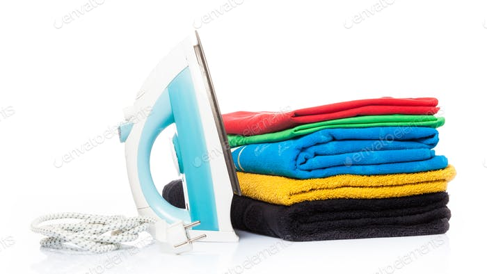 iron and clothes.  Steam iron and colored towels isolated on whi