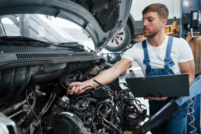 Verifying detail. Employee in the blue colored uniform works in the automobile salon