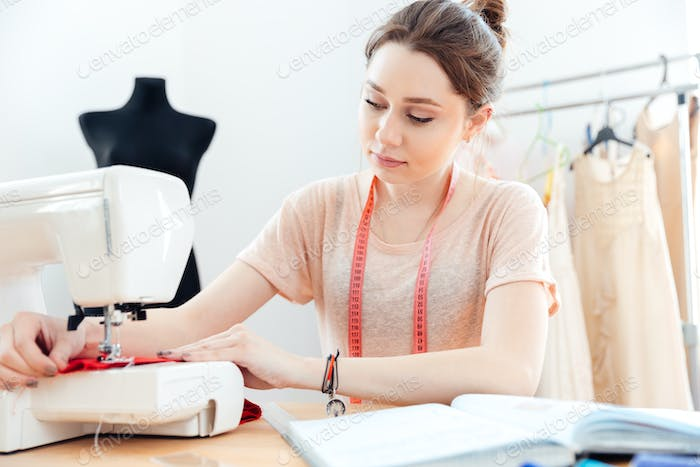 Concentrated woman seamstress sews on sewing machine
