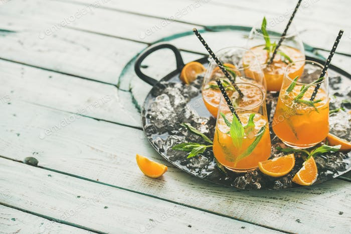 Refreshing alcoholic summer cocktail in glasses on tray, copy space