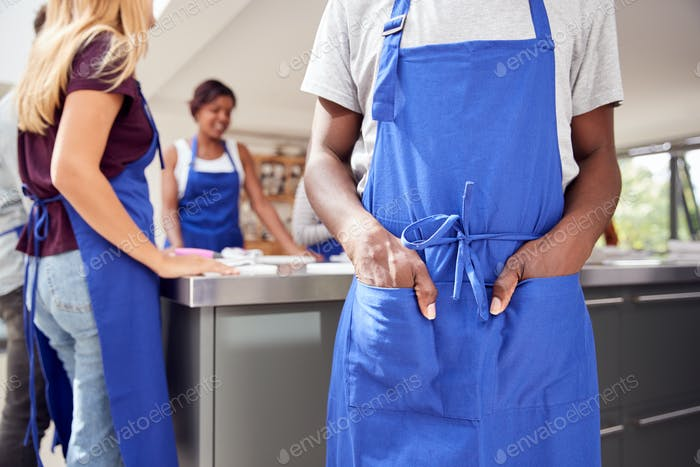 Close Up Of Man With Hands In Apron Pocket Taking Part In Cookery Class In Kitchen