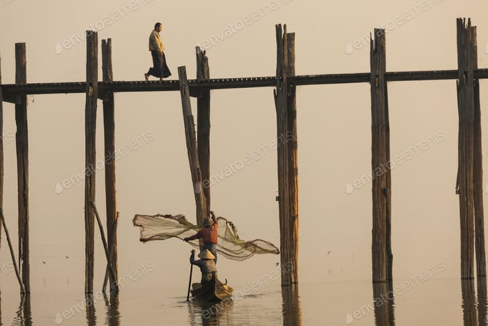 Person crossing tall teak bridge, two fisherman in fishing boat casting their net on a lake.