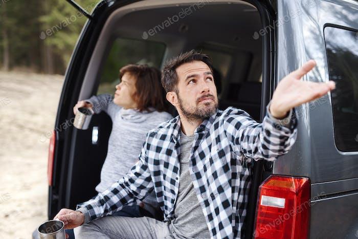 Man catching raindrop during road trip