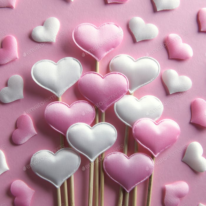 Pink textile hearts on wooden sticks closeup