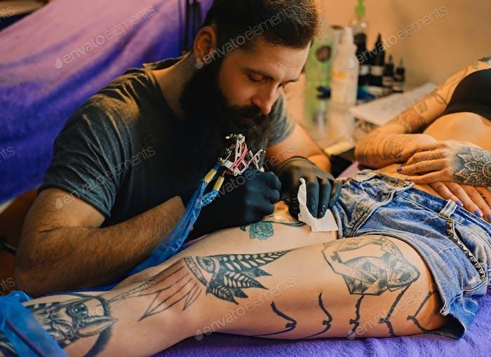 Бородатая татуировка мужчина художник делает татуировку на женскую ногу.