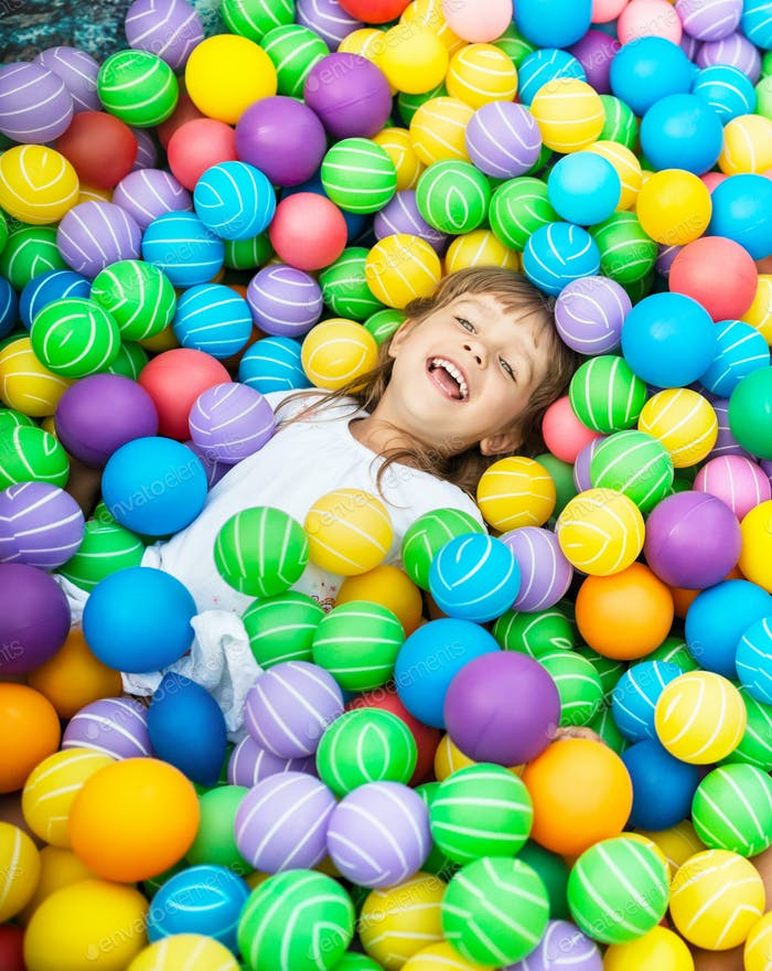 Child lying in pool with plastic balls