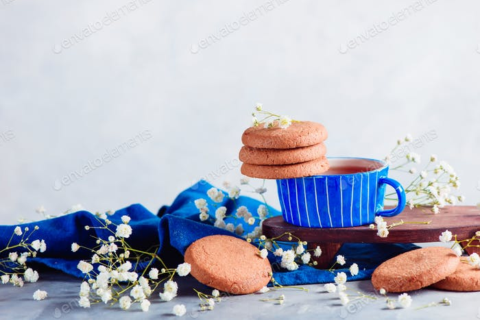 Header with cookies in a morning scene with a small blue teacup on a light background with copy