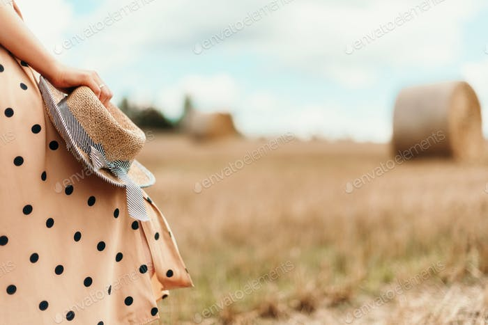 Young woman holding straw hat in wheat field. Agriculture background with copy space. Summer and
