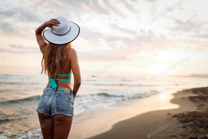 Young woman in straw hat standing on wet sand and looking sunrise