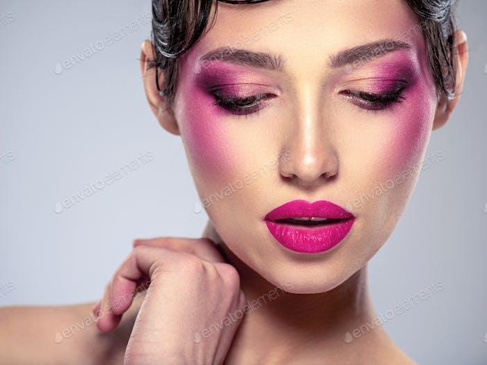 Schöne Mode Frau mit einem lila Lippenstift auf ihren Lippen.