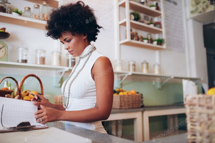 Young african woman doing accounts in juice bar