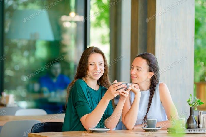 Glückliche lächelnde junge Frauen mit Kaffeetassen im Café. Kommunikations- und Freundschaftskonzept