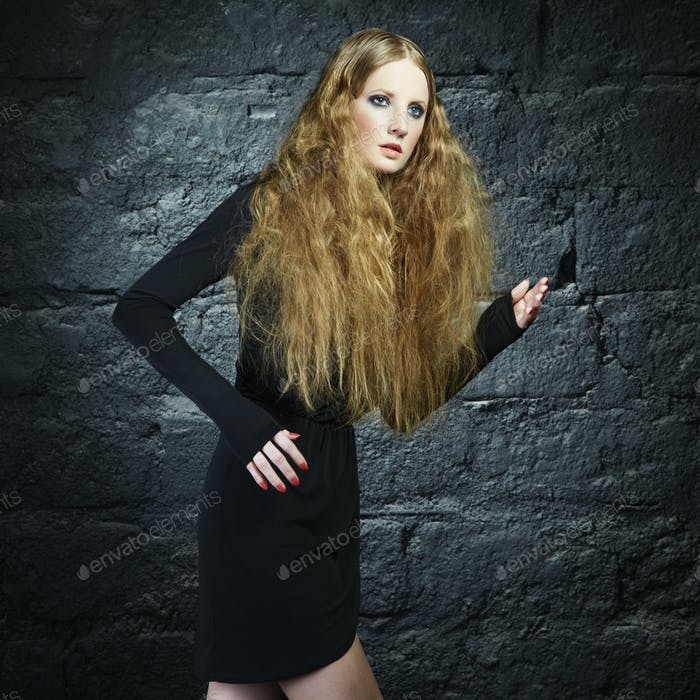 Portrait of a beautiful young woman with curly red hair