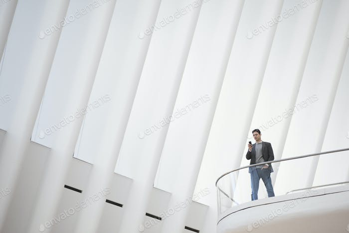 A person standing alone in an atrium by a railing on a balcony.