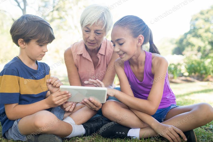 Grandmother and grand kids using digital tablet in the park