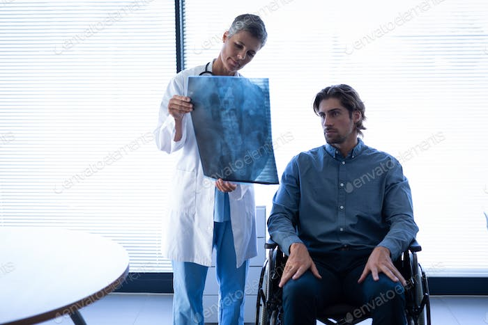 Female doctor showing x-ray report to Caucasian patient in wheelchair in clinic at hospital