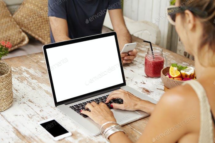 Kaukasisches Paar nutzt kostenloses WLAN im Café und genießt die Online-Kommunikation über ihre elektronisch Geräte