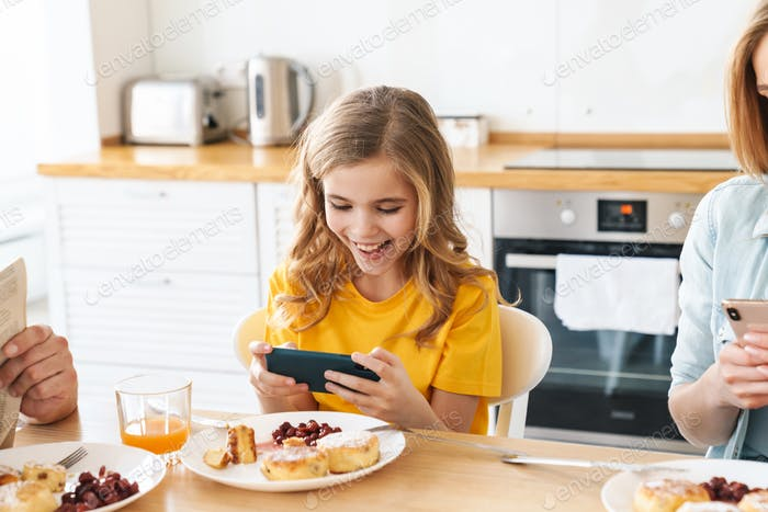 Photo of girl playing video game while having breakfast with her family