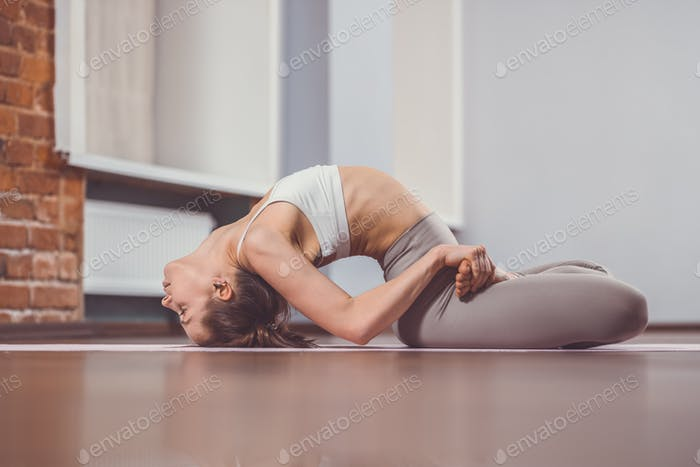Young girl practicing yoga on the floor