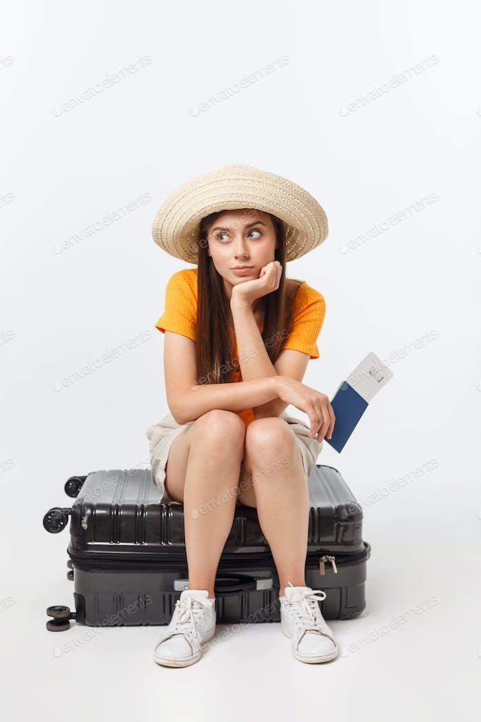 Lifestyle und Reisekonzept: Junge schöne kaukasische Frau sitzt auf Suitecase und wartet
