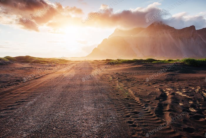 Fantastic sunset of the mountains and volcanic lava sand dunes to the beach in Stokksness. the